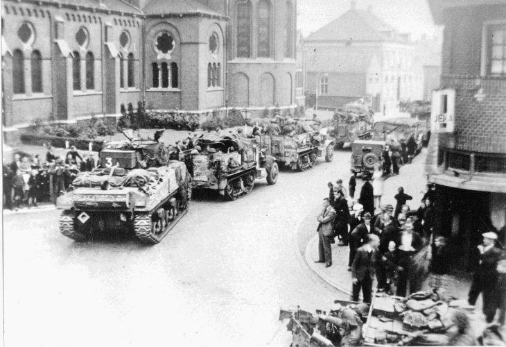 Sherman tank and 8th Rifle Brigade half-tracks passing Holy Brigida church in Geldrop. - Van der Sanden coll.