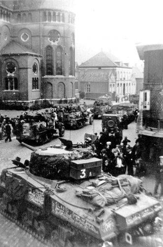 Sherman tank and 8th Rifle Brigade half-tracks passing Holy Brigida church, Geldrop - Van der Sanden coll,