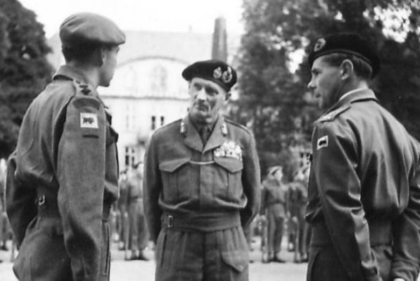 Lt.-Col. Liddell (left), shortly after the war. He took over command of the Battalion in July 1945. On his arm are the same badges as all members of the battalion, from top to bottom: the 'Rifle Brigade' black on dark green shoulder stripe, the divisional badge, showing a black bull on yellow back ground, and below that, a plain dark green arm of service stripe. On his epaulets he wears his badges of rank, a black on rifle green crown above one pip - IWM BU9897